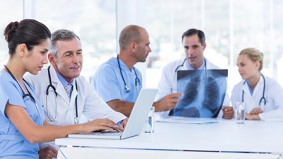 Doctors using computer whiles theirs colleagues looking at Xray in medical office