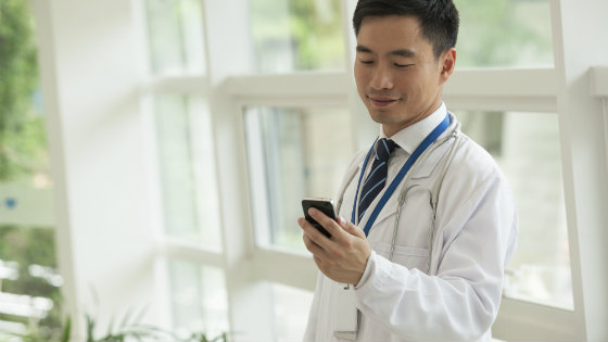 male-doctor-looking-at-smart-phone-smiling